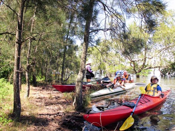 Kayakers pulled in on small low island to rest Moreton Bay
